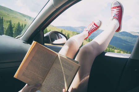 Summer Road Trip. Happy beautiful girl traveling in a car.  reads a book across  at the mountains