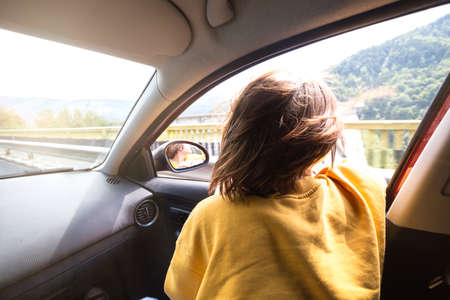 Summer Road Trip. Happy beautiful girl traveling in a car across  at the mountains. Romania