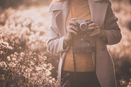 vintage autumn. girl with a vintage camera walks in the fields of fluffy dandelions at sunset Stok Fotoğraf - 129684695