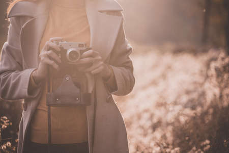 vintage autumn. girl with a vintage camera walks in the fields of fluffy dandelions at sunset Stok Fotoğraf - 129684697