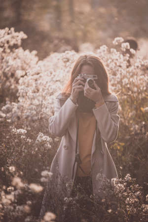 vintage autumn. girl with a vintage camera walks in the fields of fluffy dandelions at sunset Stok Fotoğraf - 129686773