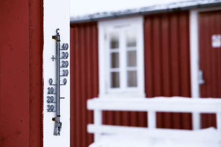 outdoor thermometer on a wooden house