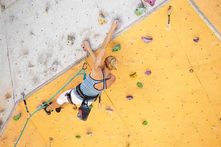 bouldering. girl climbing up the wall