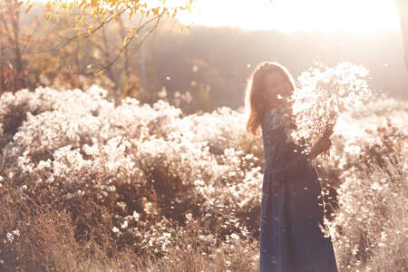 girl with flowers against the setting sun in the autumn afternoon. dandelion fluff in the autumn park.