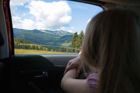 Viaje de verano por carretera. Feliz hermosa niña viajando en un coche a través de las montañas. Rumania