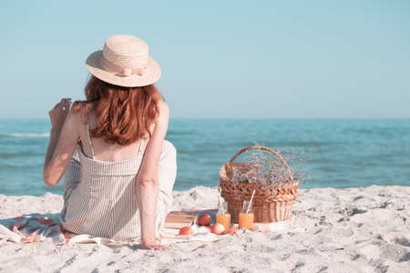 Summer - picnic by the sea. Girl in Hat and basket for a picnic with buns, apples and juice.