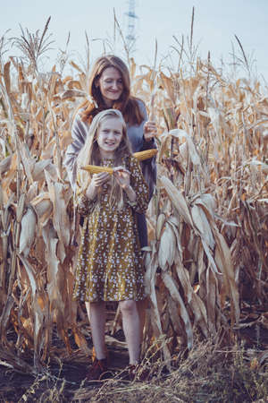 family and life outside the city. mom and daughter in a corn field.