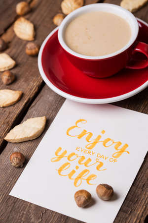 red cup of coffee and leaf shape cookies with the inscription enjoy every day of your life