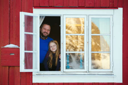 happy family. Smiling dad with daughter looking out the window of the rorbu. Lofoten Islands. Norway.