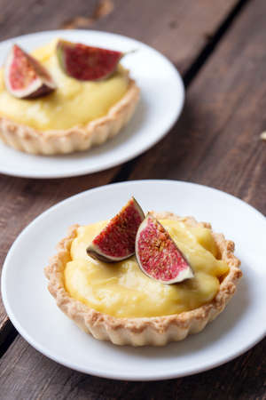 tasty tartlets with custard cream and figs on wooden background