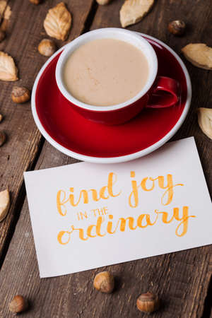 red cup of coffee and leaf shape cookies with the inscription find joy in the ordinary