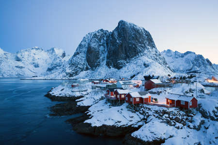 traditional norwegian red wooden house rorbu to stand on the shore of the fjord and mountains in the distance. Lofoten Islands. Norway. world travel Banque d'images