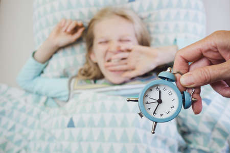 alarm clock disturbing a sleeping little girl that is defocused Фото со стока - 131339935