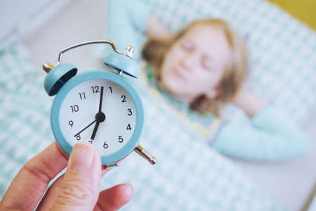 alarm clock disturbing a sleeping little girl that is defocused