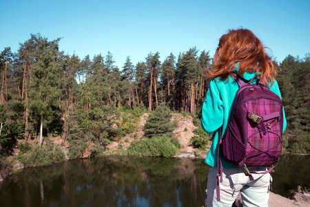 tourist girl with a backpack standing on the shore  the lake