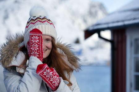 happy norwegian girl pose for the camera in red mittens with a Norwegian pattern. Lofoten islands. Norway