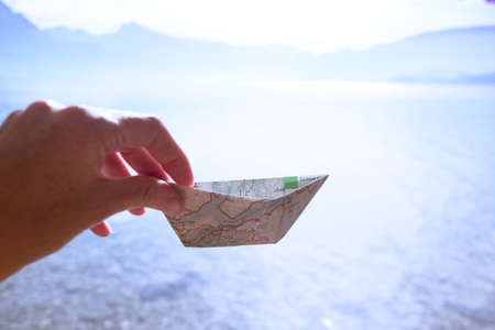 girl holding a paper boat from a map on a lake background, summer and travel Banque d'images - 133062214