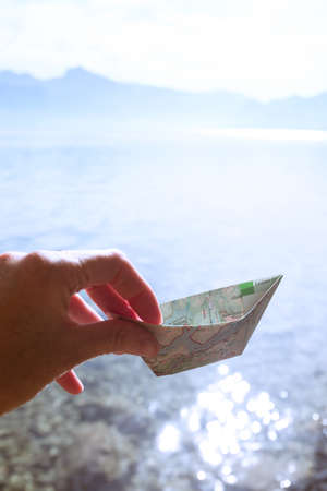 girl holding a paper boat from a map on a lake background, summer and travel Banque d'images - 133066375