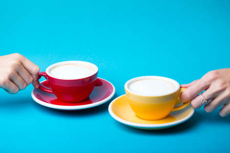 beautiful coffee yellow and red cup with cappuccino on blue background