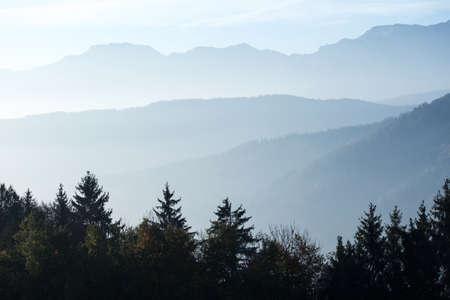 bellissimo paesaggio di montagna nelle montagne austriache. sagome di montagne nella nebbia mattutina Archivio Fotografico