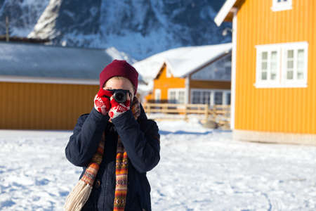 girl travels around lofoten islands and takes pictures on camera. Norway