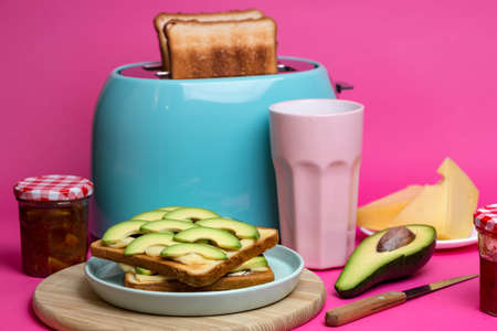bright, fun breakfast. cyan color toaster on a pink background Stock Photo