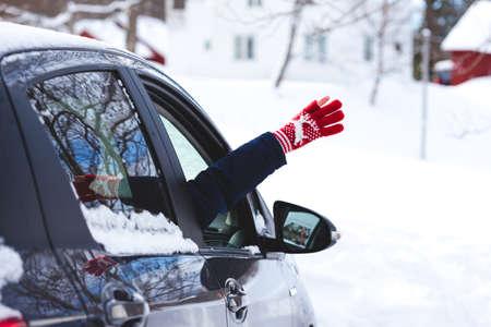Mädchenhand, die vor dem Hintergrund der Berge aus einem Autofenster späht. winterlicher Roadtrip.