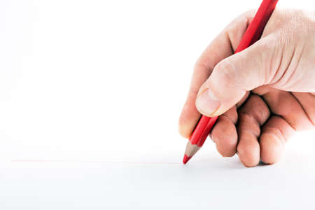 hand with the red pencil on a white background Banco de Imagens