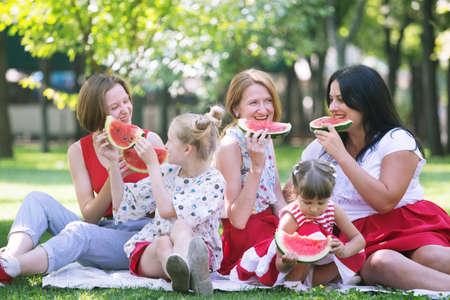 Summer -  big happy family at a picnic with watermelon.  Fun juicy summer and bright family picnic 版權商用圖片