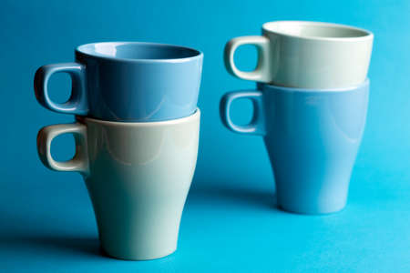 bright ceramics - cups in blue colors on a blue background