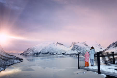 mom and daughter at the viewpoint on a Senja and mountains in the distancein at sunset time. winter norway Stock Photo - 136762538