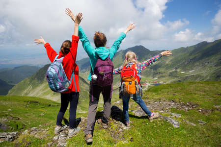 family - mother and two sisters girls hikers at the mountains Stock Photo
