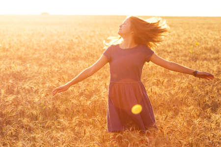 happy young girl joys at the wheat field at the evening time Archivio Fotografico