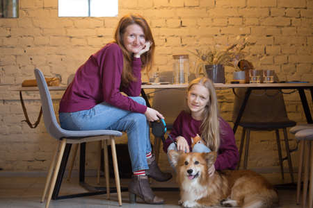holiday with family - mother with a daughter with a dog Corgi are sitting at the cafe 版權商用圖片