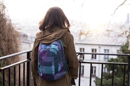 happy travel. girl with a backpack looking at paris. France