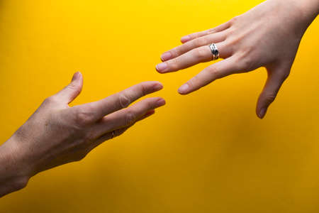 hands on a yellow background. reach out for help