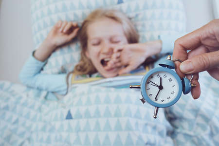 little girl lies in bed before bedtime. sleep and health