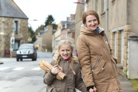 French happy mother and daughter with baguettes on the street side of the city