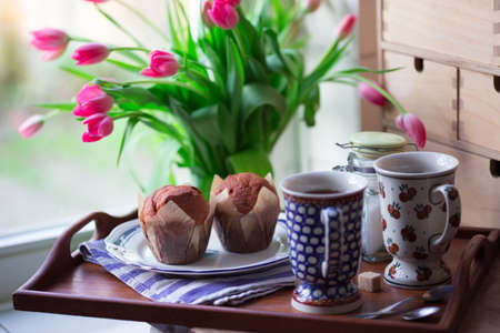 beautiful pink tulips in a vase with cupcakes and cookies in the vintage kitchen. still life