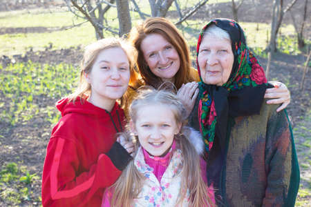 happy family. portrait of smiling senior woman, granddaughter and great granddaughters