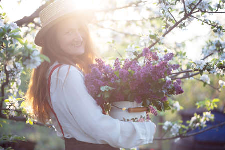 summer - beautiful girl in hat and suspenders at the garden with a bouquet of lilacs