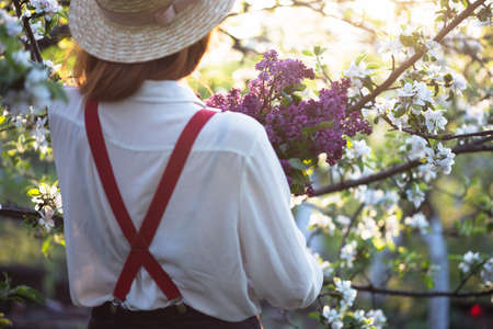 summer - beautiful girl in hat and suspenders at the garden with a bouquet of lilacs Standard-Bild
