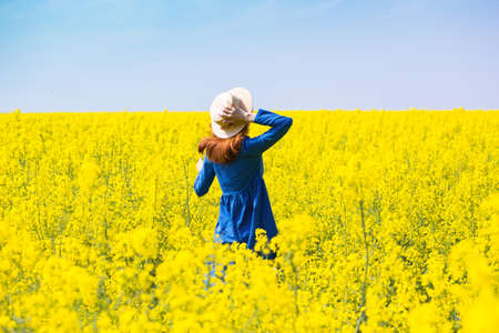 Happy girl in a hat walking in amazing field of yellow rapeseed in the countryside. Emotions Stock Photo