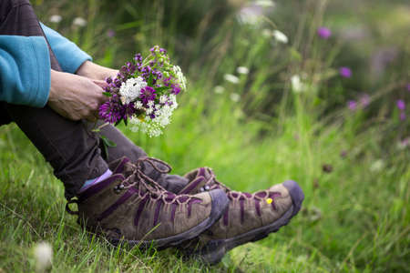 hiking boots close-up. girl tourist in boots and with a bouquet of wild flowers. active lifestyle