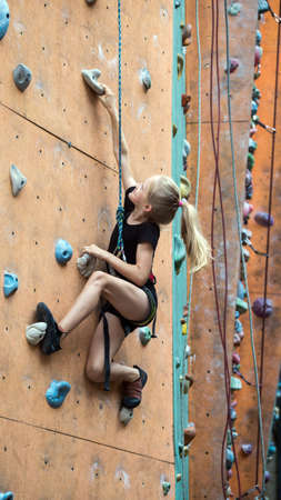 bouldering, little girl climbing up the wall and climber multicolored grips. Leisure activity