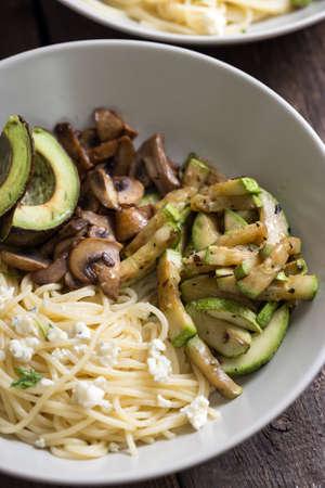 delicious dinner - pasta, mushrooms, zucchini and avocado with white wine