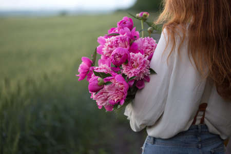 summer - Beautiful girl with a bouquet peony at the field