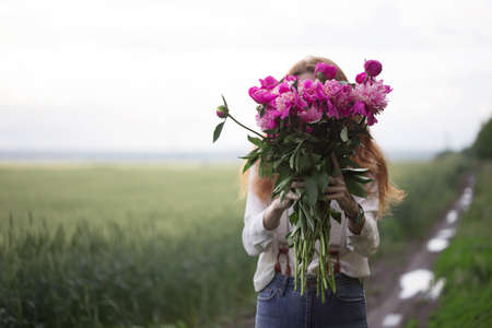 summer - Beautiful girl with a bouquet peony covers his face at the field Banque d'images