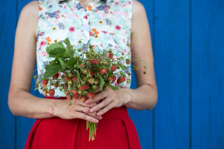 Happy girl holding bouquet of strawberry twigs