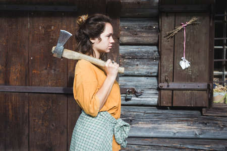 girl with an ax near a wooden house in the mountains